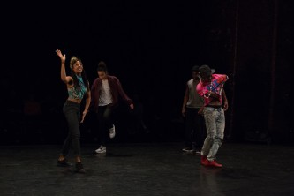 A variety of dance poses both open and closed from four people on a stage