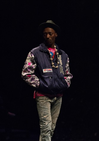 Stpryboard P standing in a purple jacket and a hat during a performance