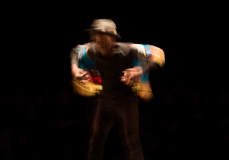 Storyboard P blurred in movement surrounded by darkness; blue red orange shirt