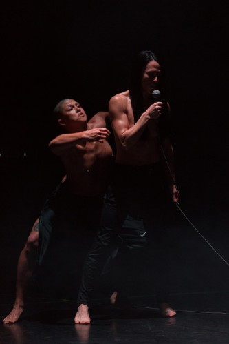 Two people in a dark room. One stands behind in a crouched stance like a pounce