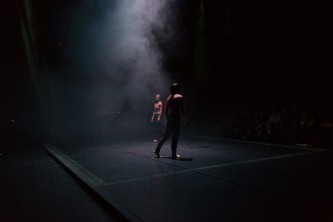 Two people face each other on the diagonal.  The room is dark with a spotlight