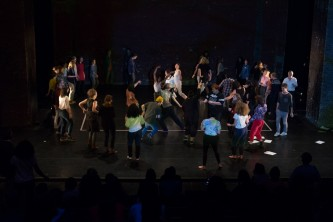 A large group of people on a stage dance and move aroud