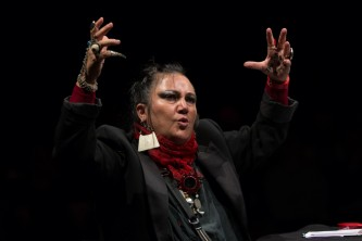 A persons holds hands in air as they speak. They wear a red scarf and jewellery