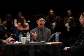 A person talks to an audience. They wear a grey cap, shirt and glasses