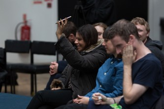 A person sits with a group. They are holding a mobile phone in the air