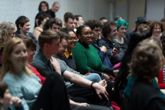 An audience listen and smile at a workshop