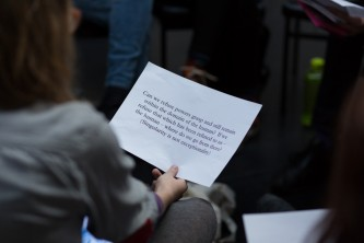 Someone holds and reads text on a paper as part of a group workshop