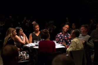 A group of people on a stage are having a discussion around a table.