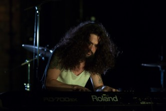 Someone with curly hair plays a keyboard