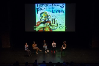 A group of people on a stage have a discussion. An image is projected behind