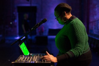 Sondra wears a green jumper and looks at a computer with glowing green screen.