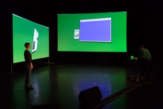 Two large screens glow green on a stage. They are at angles to one another