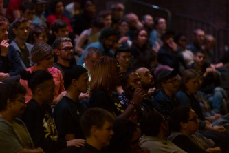 An audience member asks a question to the speakers on the stage