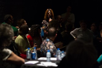 An audience member asks a question to the speakers at a table