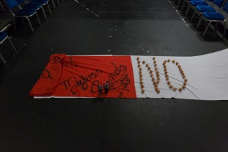 A red flag lies on top of a white sheet. Eggs are laid out to spell NO