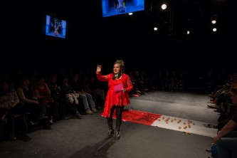 A person in a dress stands infront of an audience. There are two tv screens