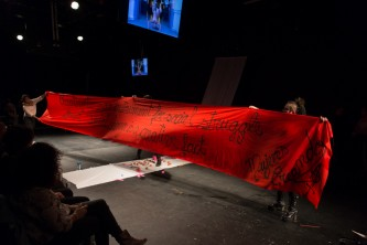 A large red banner made by Mujeres Creando