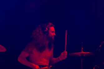 Joe Heffernan plays the drums with headphones on and a smile on their face