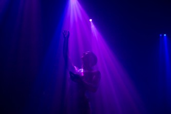 boychild performs, their arms are raised as they are bathed in purple light