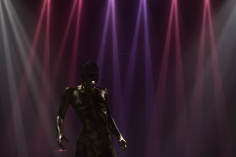 boychild performs, their skin is gold, purple and red lights are in the back