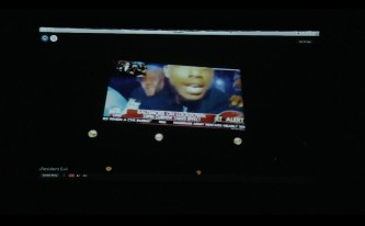 A projected screen, within it is a screen with video from the news in Baltimore