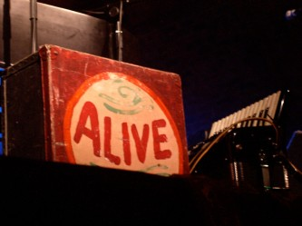 An accordion case on stage with the word 'Alive' painted on it