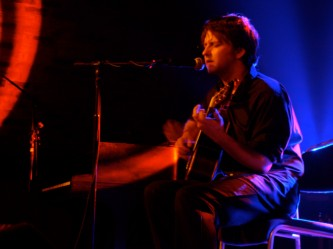 Ben Chasney playing an acoustic guitar in red and blue light