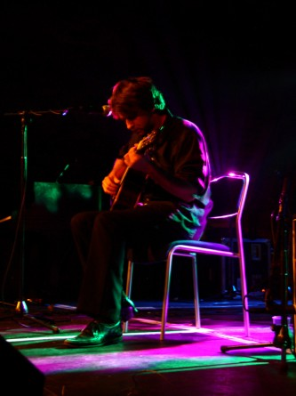A seated Ben Chasney plays guitar on a sparsely illuminated stage