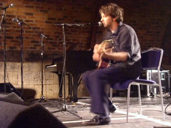 A seated Ben Chasney plays guitar on a brightly illuminated stage