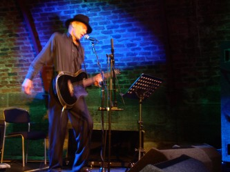 Jandek in a black stetson plays a black guitar and sings
