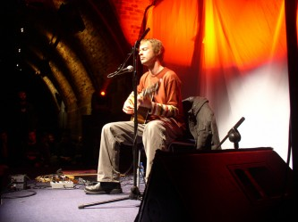Richard Youngs playing acoustic guitar on stage at INSTAL 04