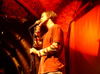 Richard Youngs stands singing into a microphone in orange light