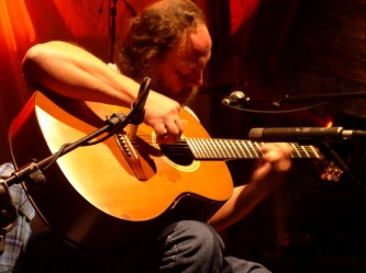 Steffen Basho-Junghans playing an acoustic guitar at INSTAL 04