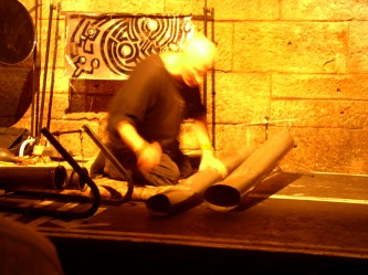 Z'ev performing on home made percussion instruments in a railway arch