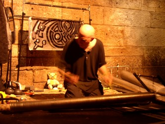 Z'EV with a small bear in a railway arch playing percussion