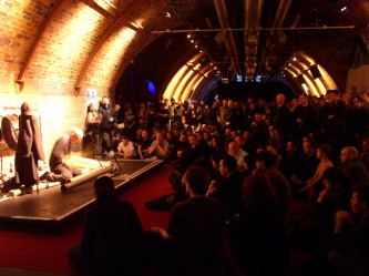 Z'EV playing percussion before an audience in a long railway arch