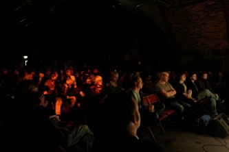 An audience sit in rows in a dark performance space