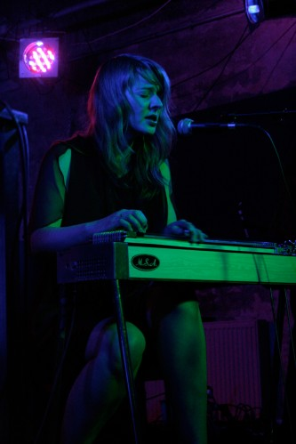 Heather Leigh Murray plays lap steel guitar and sings by green and pink light
