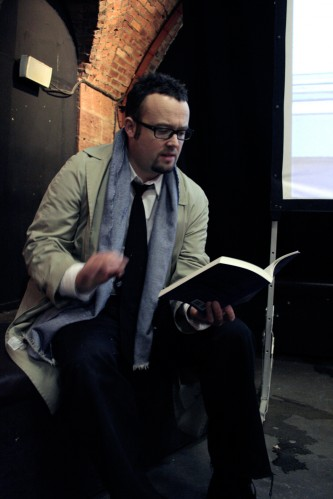 Simon Morris in suit and mac reads from a book
