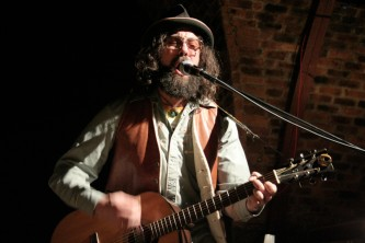 a Bearded and hatted Matt Valentine plays guitar and sings