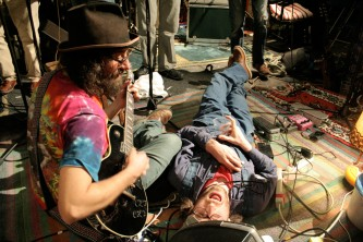 one band member is sprawled on the floor as other gather around