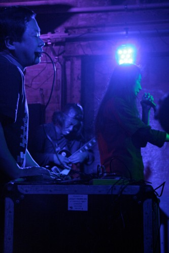 Members of Incapacitants play in a purple light