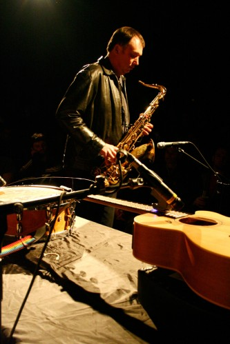 John Butcher holds and plays a saxophone with a guitar flat in the foreground