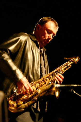 John Butcher holds and plays a saxophone, one shoulder hunched up