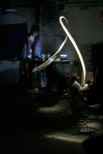 A performer in a dark space plays electronics, a light streak in the foreground