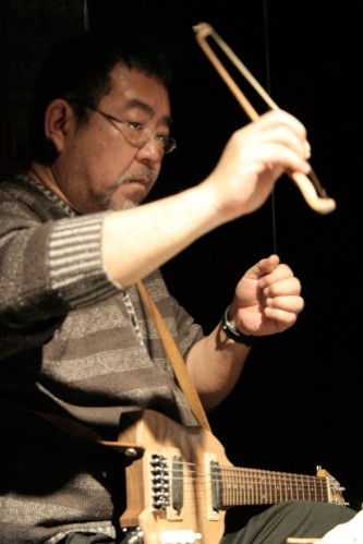 Kei Shii plays a wire in the air with a bow, a handmade guitar on his lap