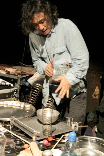 Kazuo Imai plays a tin, springs and objects in front of him