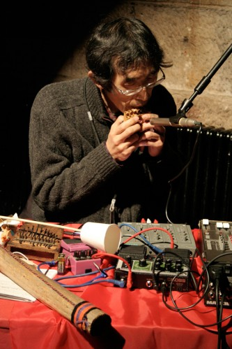 Tomonao Koshikawa plays a bamboo pipe a table of objects in front