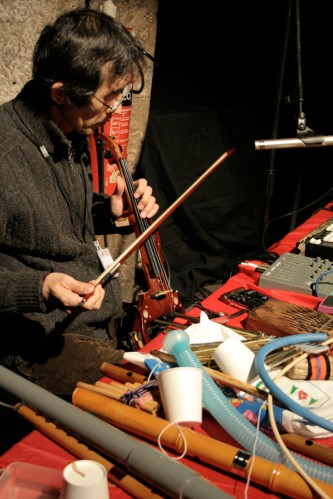 Tomonao Koshikawa plays a small violin a table of objects in front