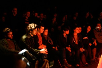 Rows of audiences watch a performance in a dark space, lit red